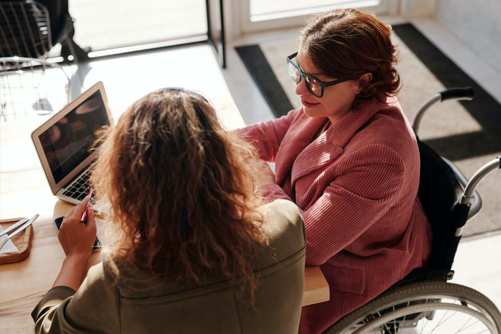 Woman in red sweater wearing black framed eyeglasses sitting on wheelchair with friend