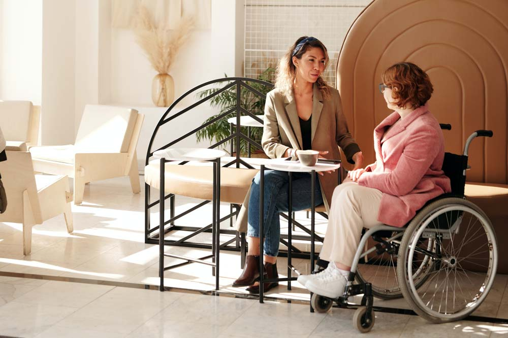 Woman in wheelchair sitting in cafe with friend